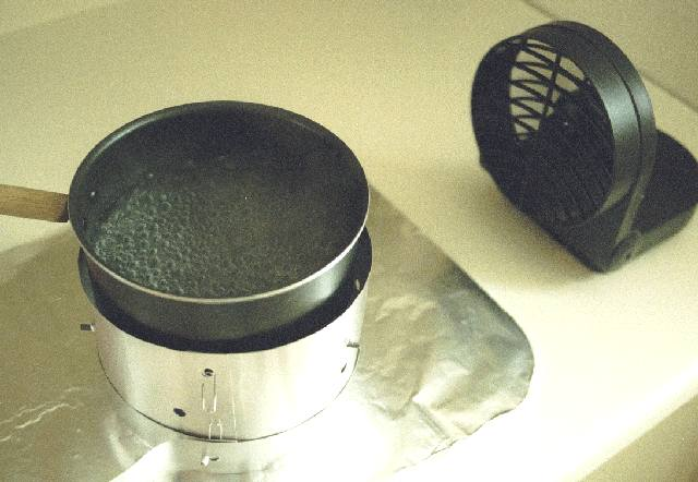 The simmer control is on the outside of the stove and can be adjusted without removing the pot.
